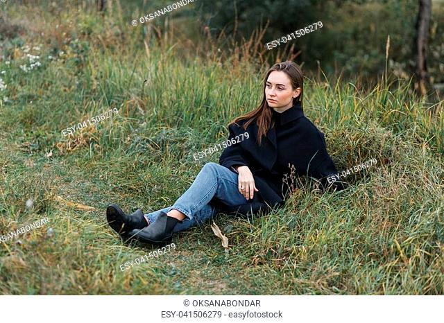 Brunette woman lying on dark green autumn grass. Casual fashion style