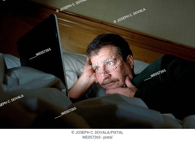 Man in bed looking at laptop