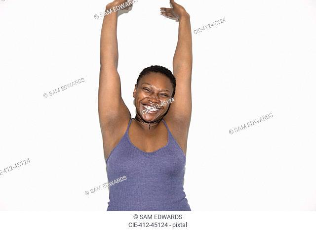 Portrait exuberant woman with arms raised