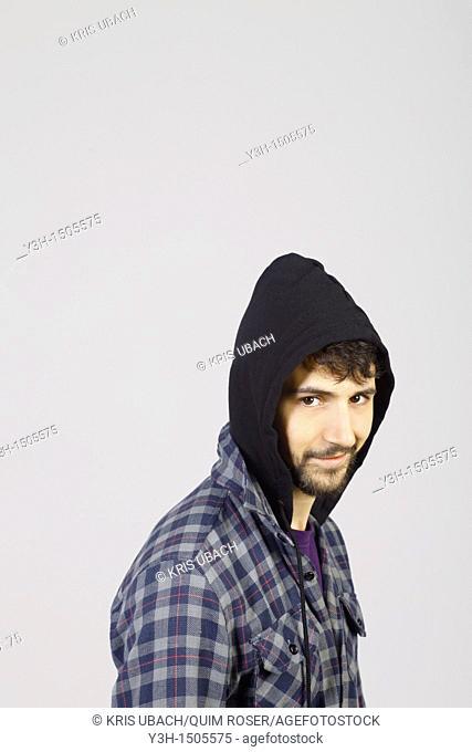 Studio shot of young man, hooded jacket