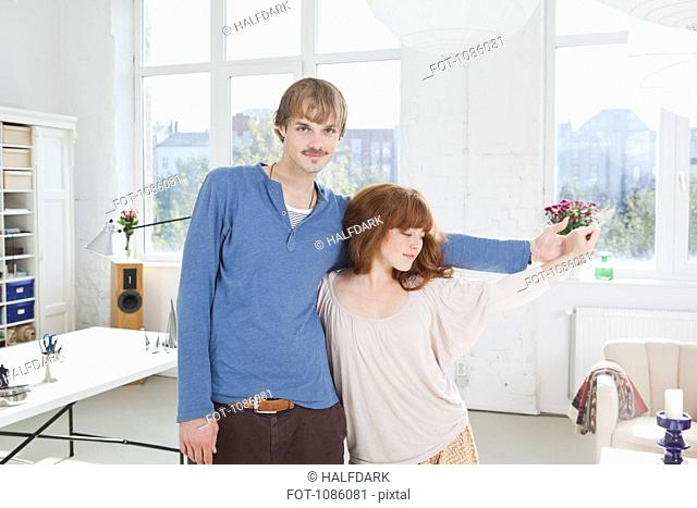A young playful couple standing side by side holding hands