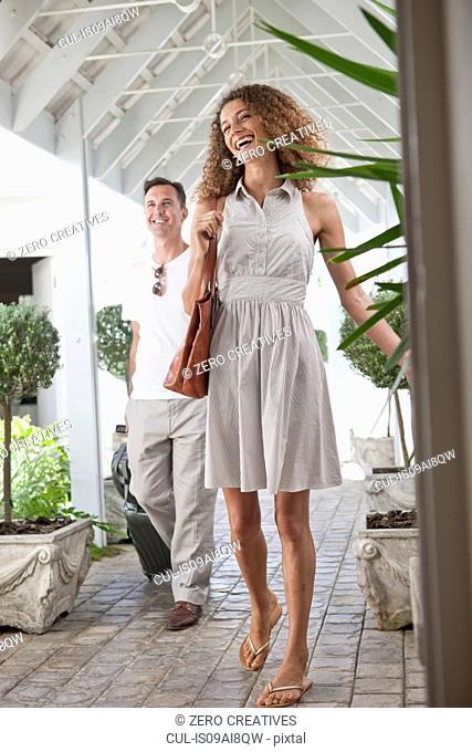 Couple arriving at beach house apartment with suitcases
