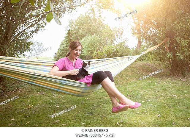 Relaxed woman with cat in hammock