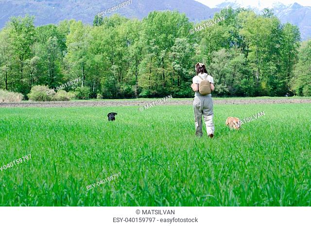 Travel woman with scarf and backpack on the green field with grass and trees and two dogs
