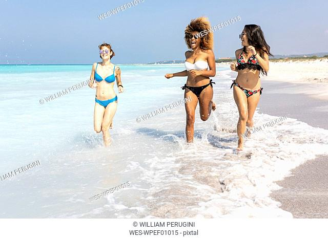 Girl friends having fun on the beach, running at the sea