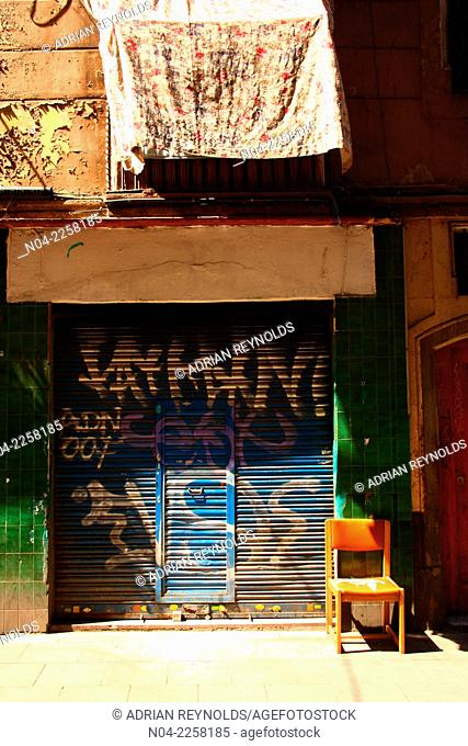 Colorful closed shop with chair and hanging laundry, El Raval, Barcelona, Catalonia, Spain