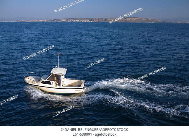 Fishing boat going back to the harbor. Santa Pola in background, Tabarca island. Alicante province. Spain