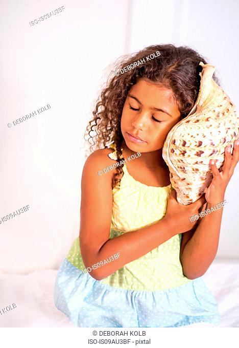 Girl holding seashell to ear, eyes closed listening