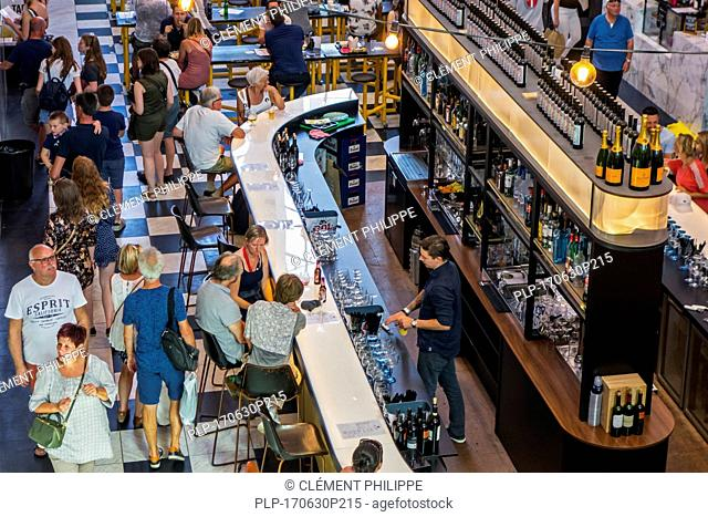 Aerial view over bar counter and bartender serving drinks to customers in the Holy Food Market in Ghent / Gent, Flanders, Belgium