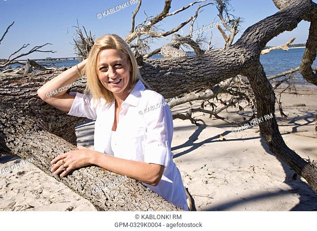 Mature woman on beach next to tree branches
