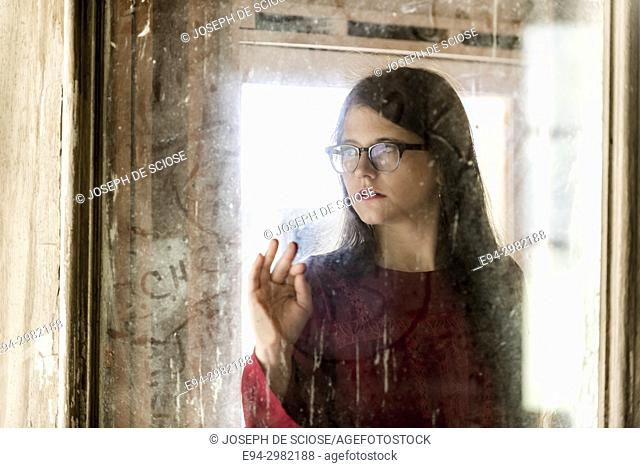 A blurry portrait of a 26 year old woman wearing a straw hat and large glasses looking through a dirty window