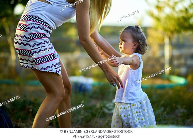 young toddler walking into arms of mother during sunset. Australian ethnicity. During holiday stay in Hersonissos, Crete, Greece
