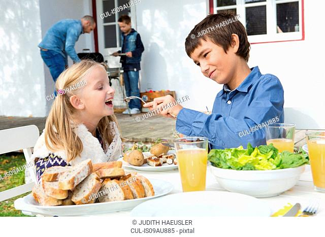 Teenage boy feeding sister at garden barbecue table