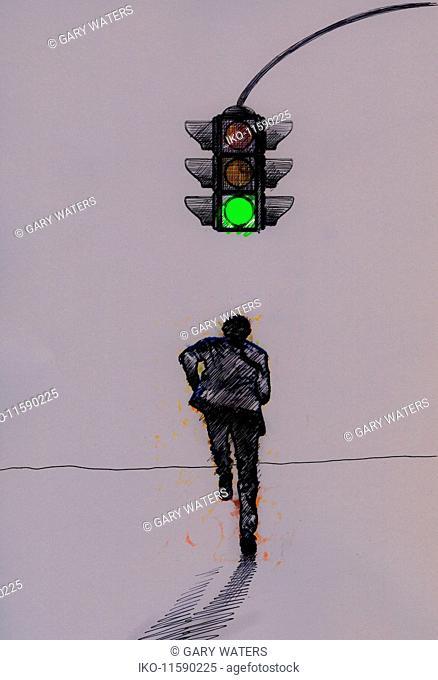 Businessman running under green traffic signal