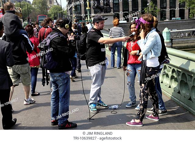 Young femail tourists being filmed and interviewed on Westminster Bridge, London, England on 28th April 2011