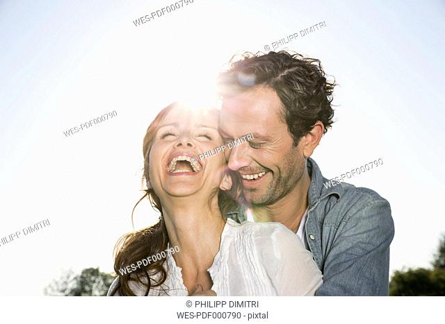 Laughing couple at backlight