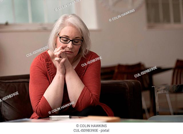 Woman looking upset on couch