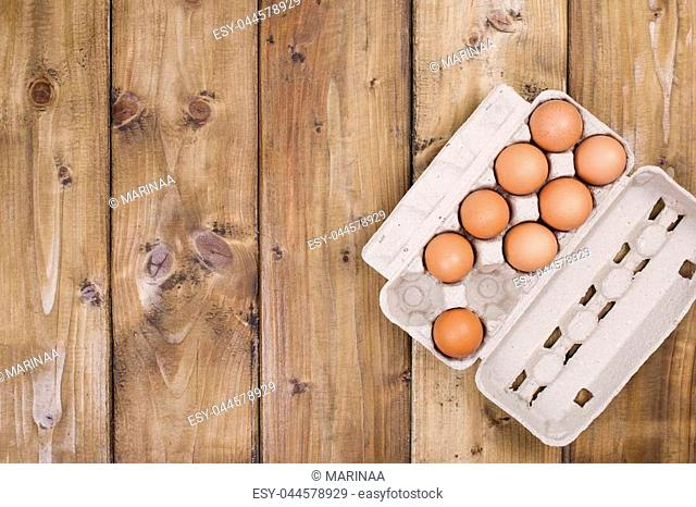 Preparation of homemade cakes on a wooden background. Ingredients and accessories for the kitchen and at home. Eggs in a box and space for text