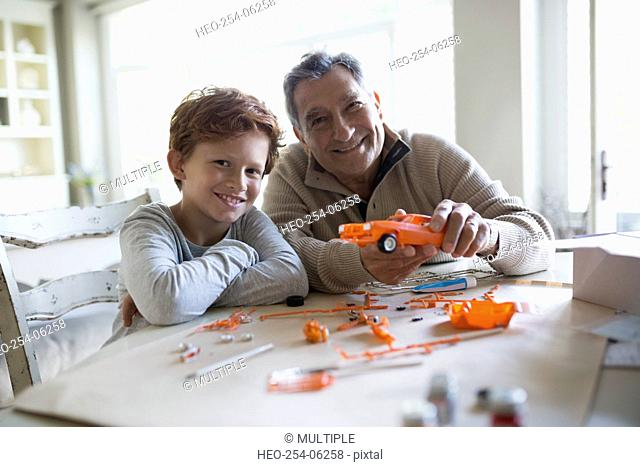 Portrait smiling grandfather and grandson assembling model cars