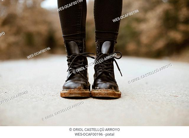 Woman wearing black boots, partial view
