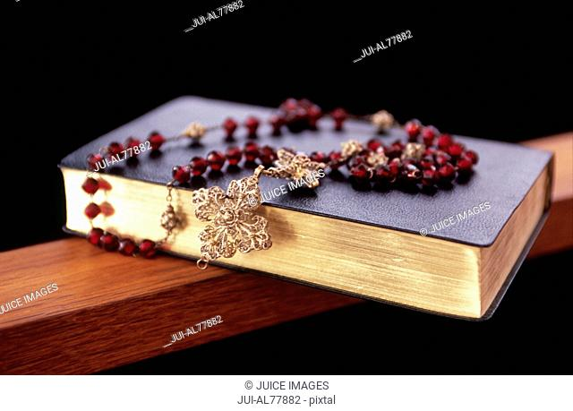 Rosary beads on top of a Bible