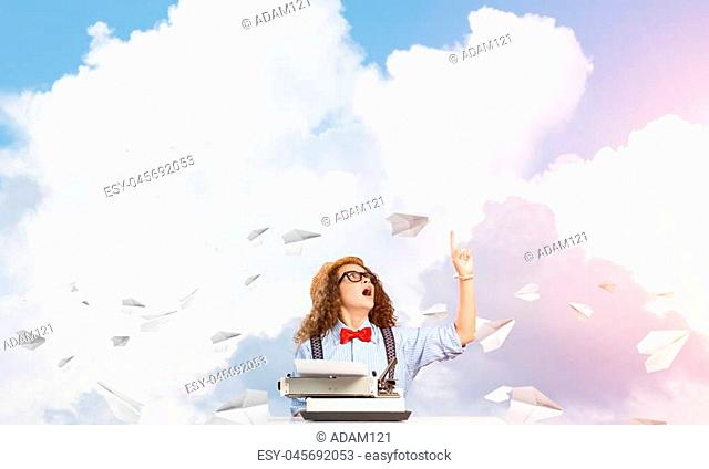 Young and beautiful woman writer in hat and eyeglasses using typing machine while sitting at the table among flying paper planes with cloudy skyscape on...
