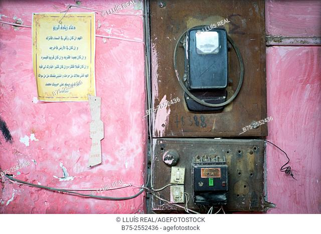 Pink wall with an electric meter, cables and a text written in Arabic. Fez medina, Morocco, Africa