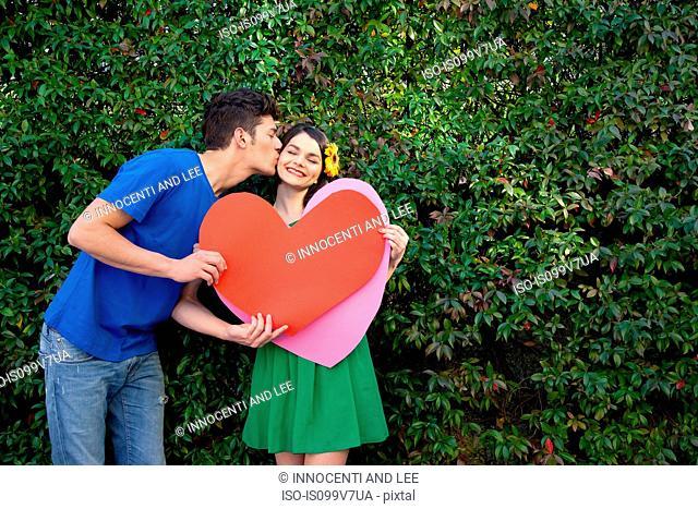 Couple holding heart shape, man kissing woman
