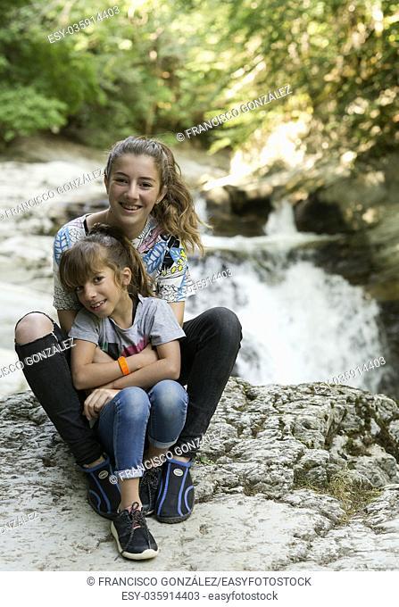 Sisters sitting on rocks next to a river in the Seva de Irati de Navarra; Spain