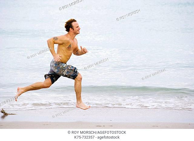Young man running at the beach