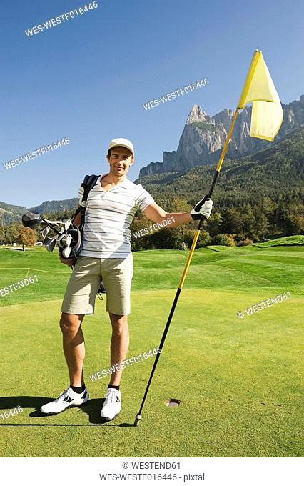 Italy, Kastelruth, Mid adult man on golf course, portrait