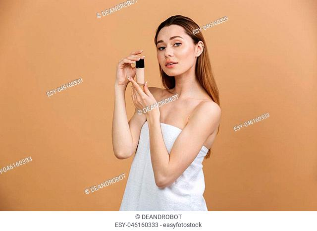 Beauty portrait of beautiful caucasian woman in white towel looking at camera and holding concealer bottle near face isolated over beige background