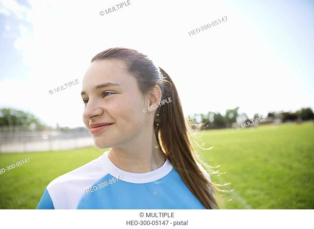 Smiling middle school girl soccer player looking away on sunny field