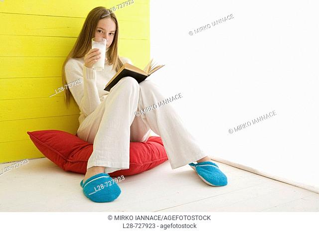Woman reading book and drinking milk