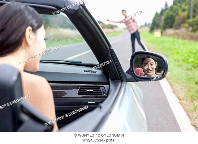Back p of young smiling woman looking in side mirror and a young man hitchhiking