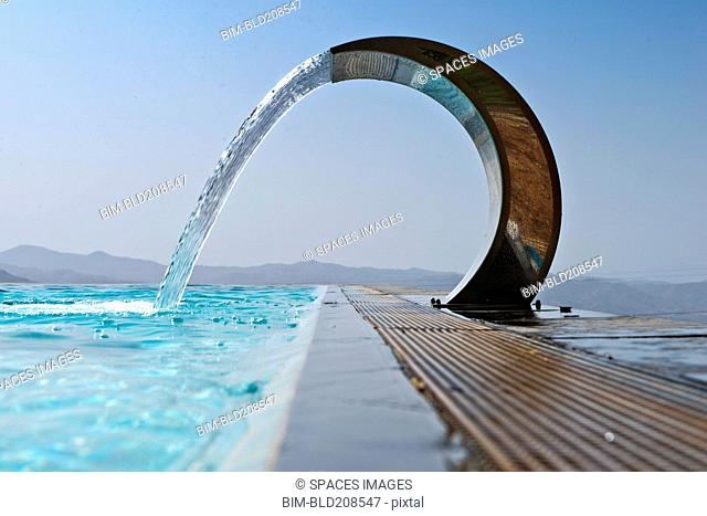 A curved stainless steel water fountain with water flowing
