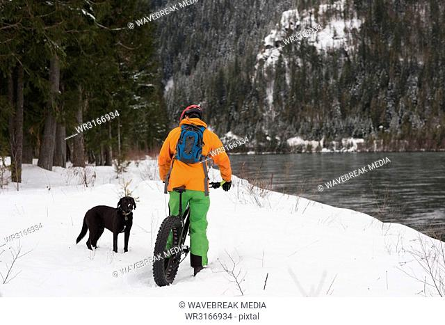 Man with bicycle looking at dog on a snowy landscape