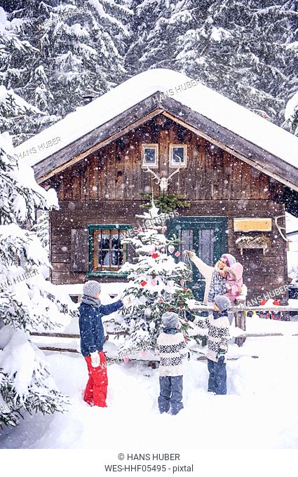 Austria, Altenmarkt-Zauchensee, family decorating Christmas tree at wooden house