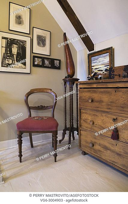 Antique wooden dresser, red upholstered chair on the upstairs hallway and walls decorated with paintings inside an old 1809 cottage style residential home