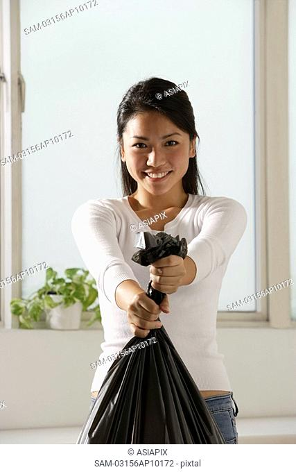 Young Asian woman holding trash bags
