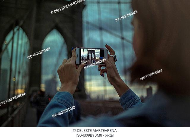 Woman photographing Brooklyn bridge using smartphone, New York, United States, North America
