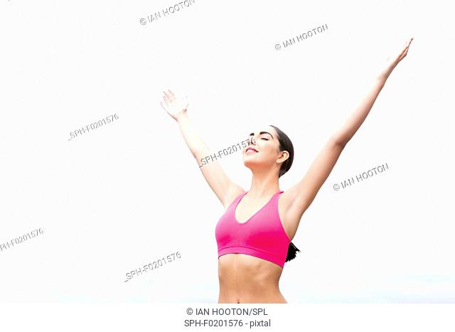 Woman wearing sports bra with arms up