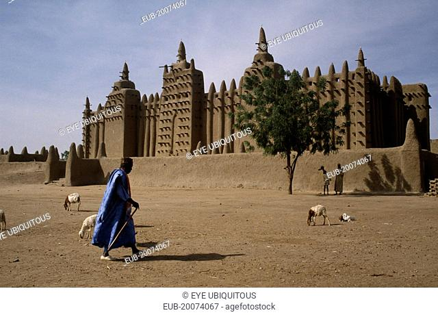 Grand Mosque with man walking past and sheep in the foreground