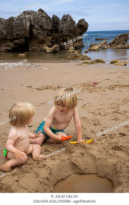 Two Young Children Playing in Sand at Beach