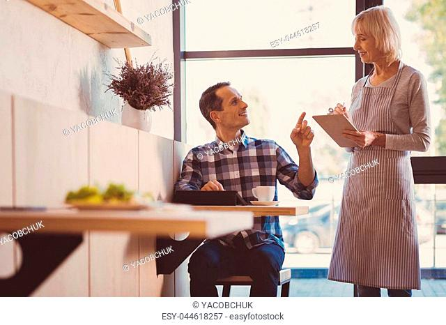 I am hungry. Pleasant young man sitting at the table in a cafe, using a tablet and ordering food from a waitress while she smiling at him