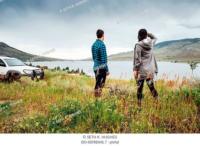 Couple standing beside Dillon Reservoir, looking at view, Silverthorne, Colorado, USA