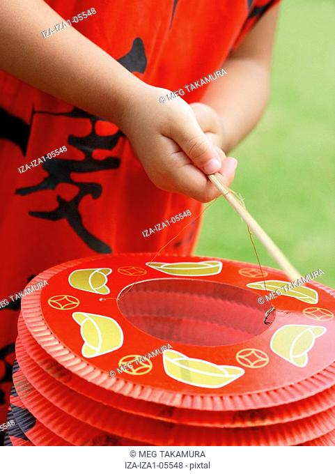 Mid section view of a girl holding a Chinese lantern with a stick