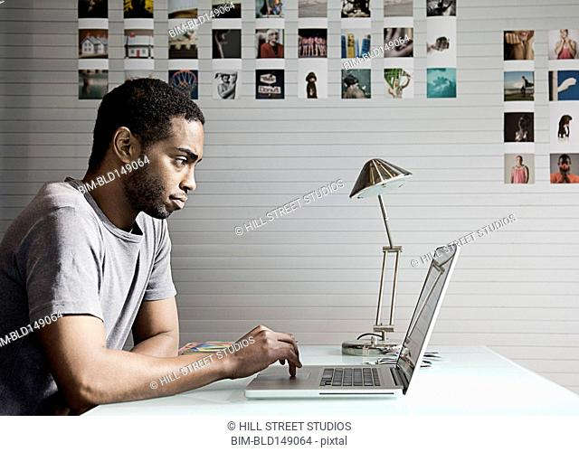 Black man sitting at desk using laptop