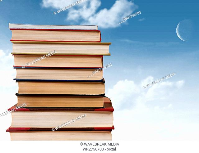 Books stacked by blue sky