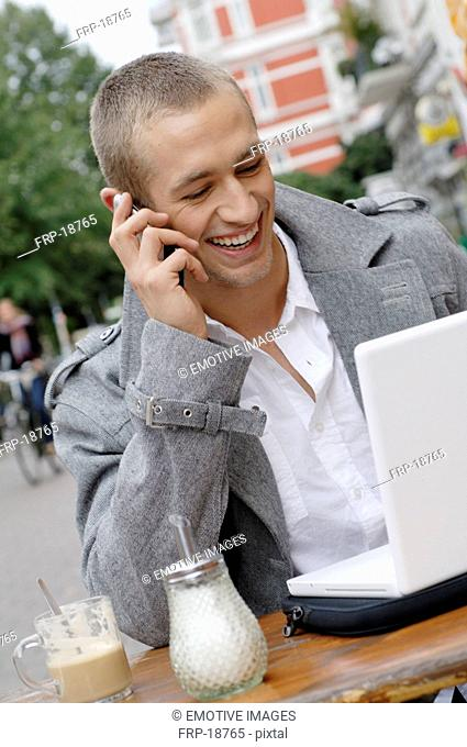 Young man using laptop and cell phone at an outdoor cafe